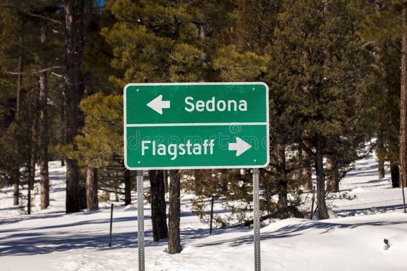 FEBRUARI 2019 - VÄSTRA DELSTATERNA - USA - den Americana vägrenen Amerika visar tecknet till flaggstången och Sedona i snö arkivfoto