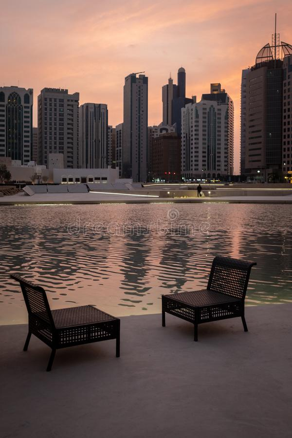 evening view of Empty chairs near water pool agianst abu dhabi city scpae stock photography