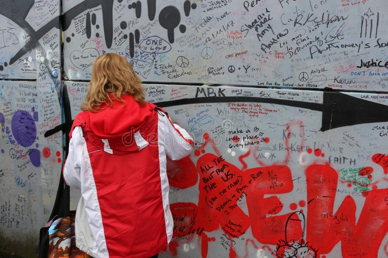February 20 2018, Belfast Northern Ireland: Editorial photograph of a women signing the peace wall that is situated in stock image