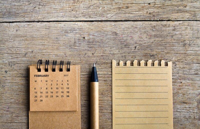 February. Calendar sheet on wooden background. stock photos
