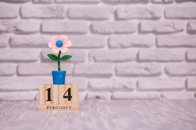 February 14. Day 14 of month on wooden calendar with toy flower on white brick background. Happy Valentines day. royalty free stock photography
