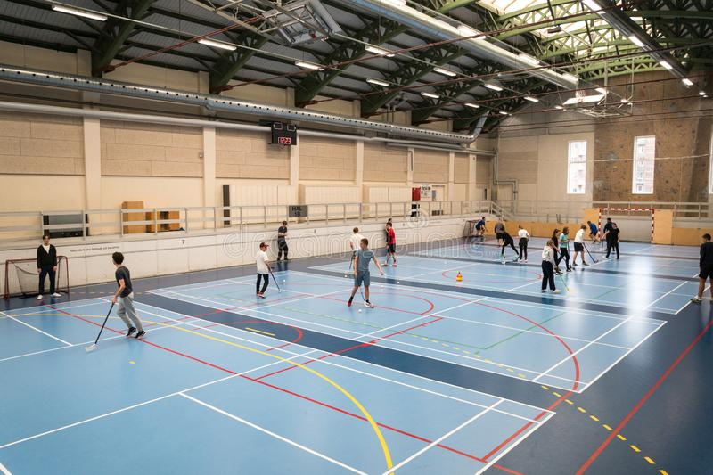 February 21, 2019. Denmark. Copenhagen. Team game with stick and ball Floorball or hockey in hall. Inside training in the gym of. The school college. Group of stock photography