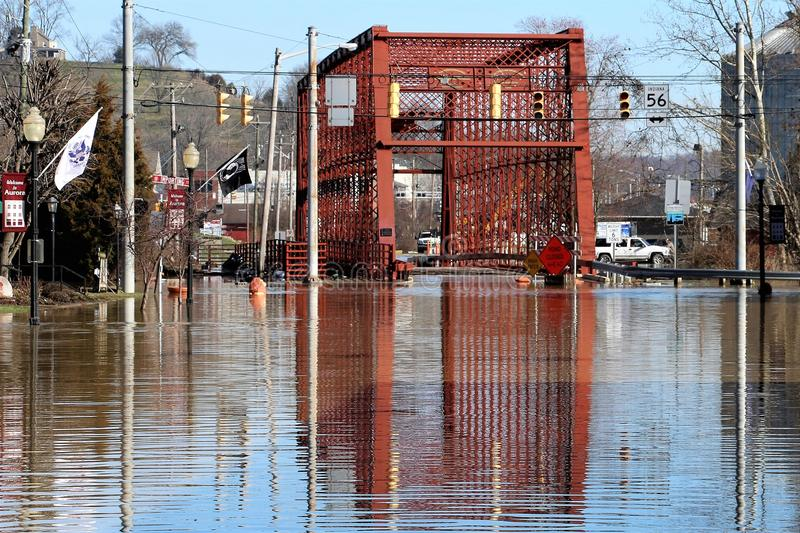 Flood waters over bridge in Aurora, Indiana. February 2018 flooding of Aurora, Indiana from the Ohio River. Flood waters over bridge with reflection stock photo