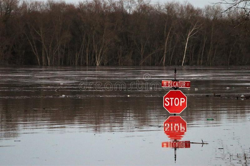River flood up stop sign in Aurora, Indiana at night. February 2018 flooding of Aurora, Indiana from the Ohio River. River flooding road to stop sign. Reflection stock images