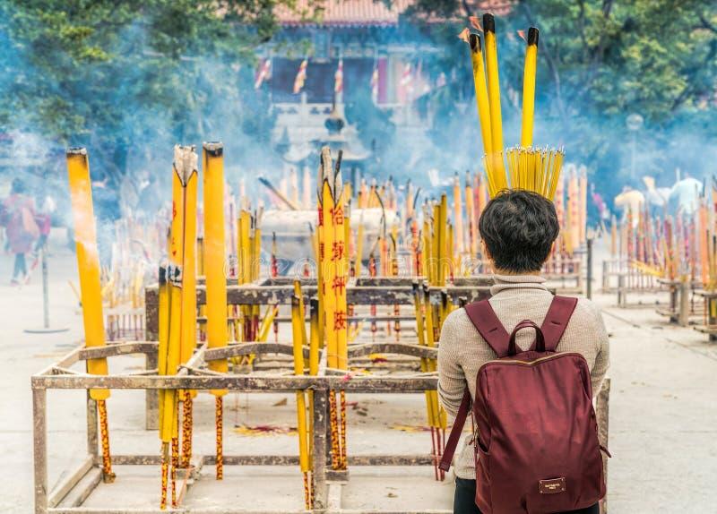 Woman Burning Yellow Incense Sticks royalty free stock photo
