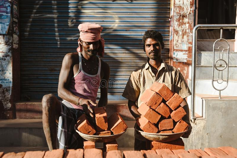 23 february 2018 Madurai, India, two indian workers in outdoors with plates ful of bricks royalty free stock photo