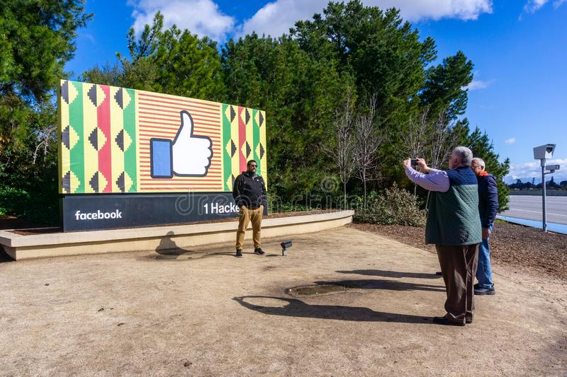 February 10, 2019 Menlo Park / CA / USA - Group of people taking photos with the Facebook logo customized for black history month. Located outside the Company`s royalty free stock images