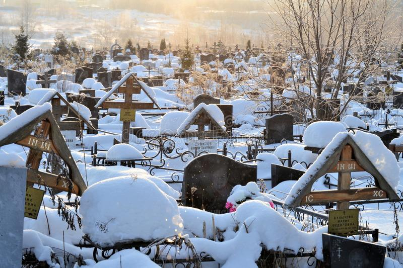 Crosses in a cemetery, monuments of the dead, a cemetery in winter, wreaths, artificial flowers. Russia stock photo