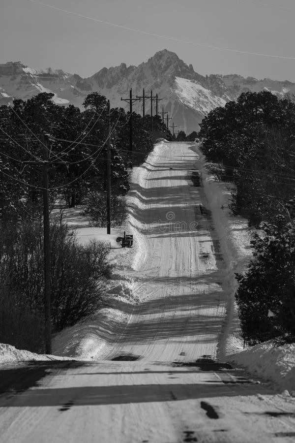 FEBRUARY 24, 2019 - RIDGWAY COLORADO USA - Winter snowy road through deep snow leads to San Juan Mountains leaving tire tread trai royalty free stock photos