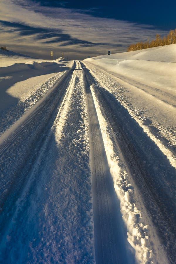 FEBRUARY 24, 2019 - RIDGWAY COLORADO USA - Winter snowy road through deep snow leads to San Juan Mountains leaving tire tread trai. Ls stock images