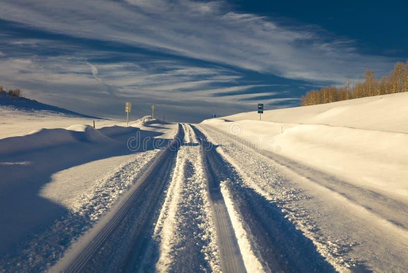 FEBRUARY 24, 2019 - RIDGWAY COLORADO USA - Winter snowy road through deep snow leads to San Juan Mountains leaving tire tread trai. Ls royalty free stock photography