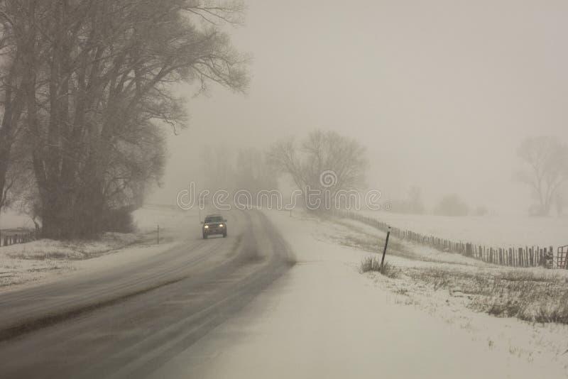 FEBRUARY 24, 2019 - RIDGWAY COLORADO USA - Winter snowy road through deep snow leads to San Juan Mountains leaving tire tread trai stock photo