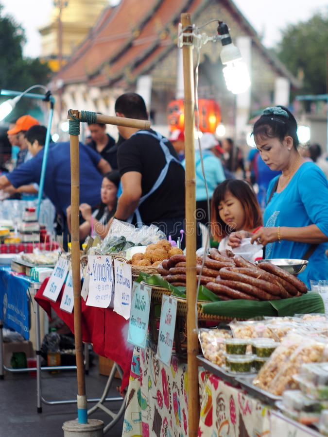 Traditional food street and souvenir goods market lifestyle in cute tourist destination town: NAN province of THAILAND. February 2, 2018: sellers prepare their royalty free stock photo