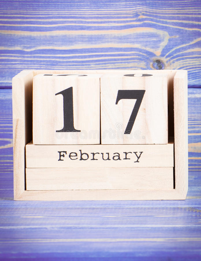 February 17th. Date of 17 February on wooden cube calendar. Purple board as background stock photography