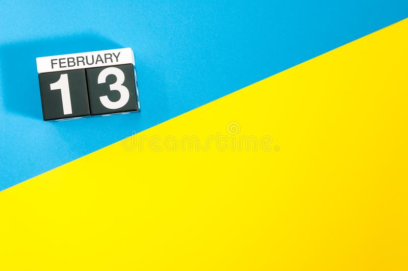 February 13th. Day 13 of february month, calendar on blue and yellow background flat lay, top view. Winter time. Empty. Space for text royalty free stock images