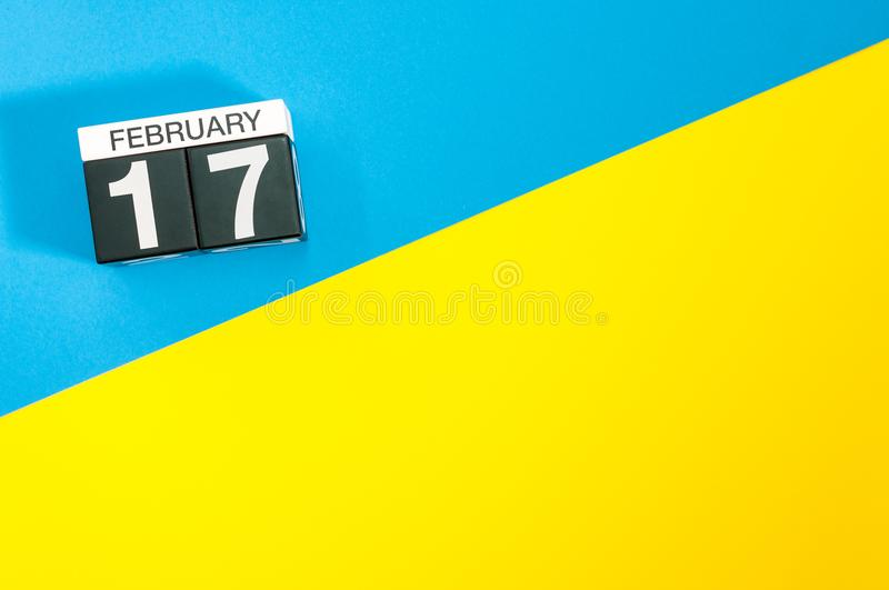 February 17th. Day 17 of february month, calendar on blue and yellow background flat lay, top view. Winter time. Empty. Space for text stock photo