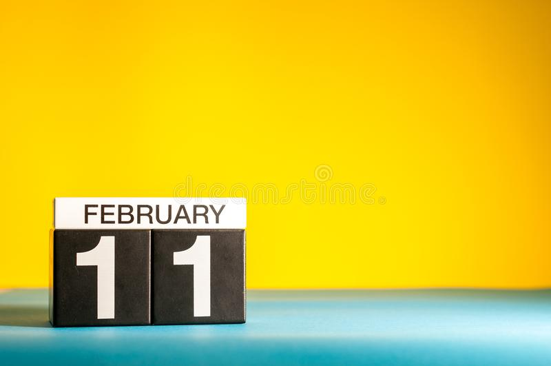 February 11th. Day 11 of february month, calendar on yellow background. Winter time. Empty space for text.  royalty free stock image
