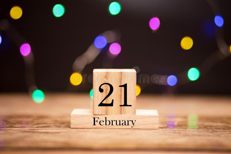 February 21th. Day 21 of february month set on wooden calendar at center of dark background with garland bokeh. Winter time. Empty space for text, mockup stock photos