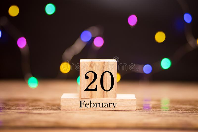 February 20th. Day 20 of february month set on wooden calendar at center of dark background with garland bokeh. Winter time. Empty space for text, mockup royalty free stock photography