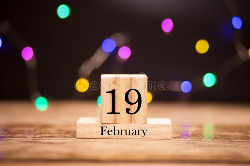 February 19th. Day 19 of february month set on wooden calendar at center of dark background with garland bokeh. Winter time. Empty space for text, mockup stock photography