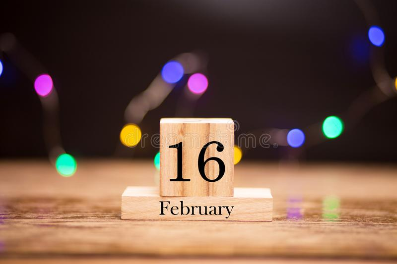 February 16th. Day 16 of february month set on wooden calendar at center of dark background with garland bokeh. Winter time. Empty space for text, mockup royalty free stock images