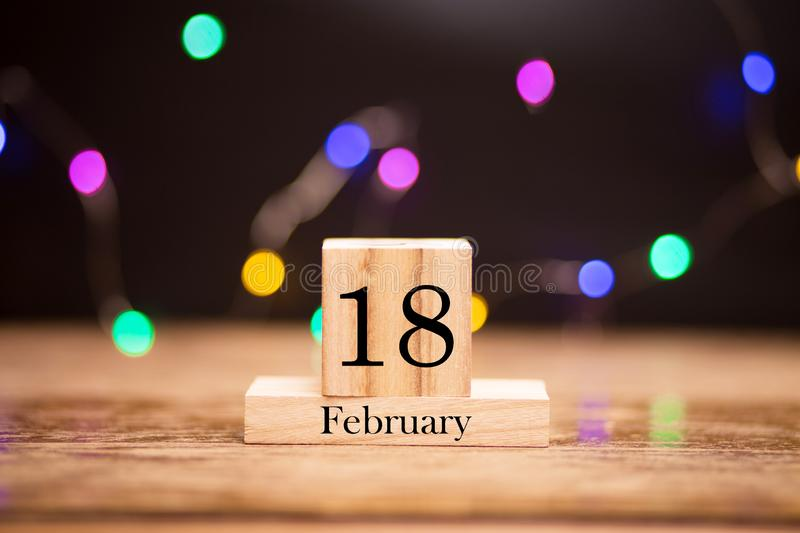 February 18th. Day 18 of february month set on wooden calendar at center of dark background with garland bokeh. Winter time. Empty space for text, mockup stock photography