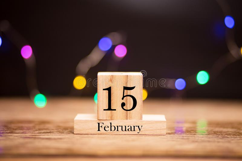 February 15th. Day 15 of february month set on wooden calendar at center of dark background with garland bokeh. Winter time. Empty space for text, mockup royalty free stock photography