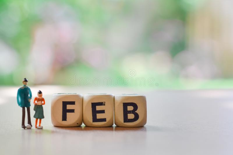 February on wooden block with Couple love of miniature people, small model human figure standing on floor with green blurry stock photography