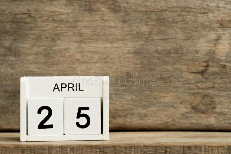 Fecha blanca 25 del calendario de bloque actual y mes abril en el fondo de madera foto de archivo