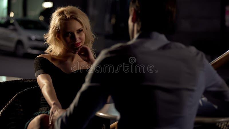 Fecha de la noche en el restaurante, la mano de la mujer conmovedora masculina, el ligar del amo de la recogida fotografía de archivo