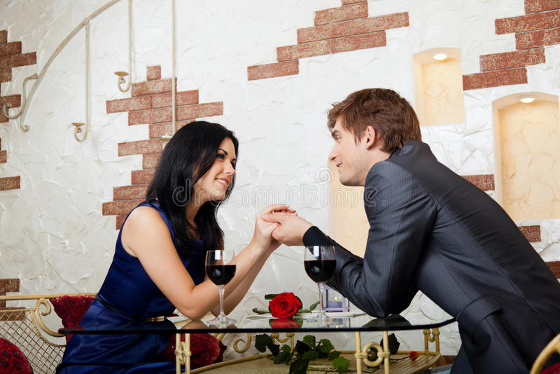 Fecha romántica de los pares felices jovenes en el restaurante imagenes de archivo