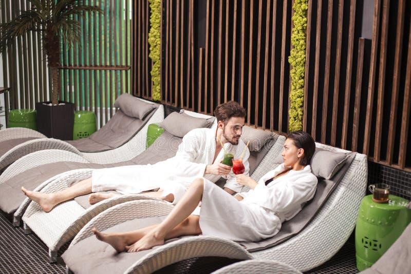 Fecha romántica inusual el varón y la hembra bonitos están bebiendo el jugo después de sauna fotografía de archivo