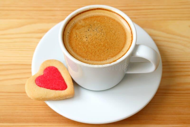 Fechado acima do café do café com coração deu forma às cookies servidas na tabela de madeira foto de stock