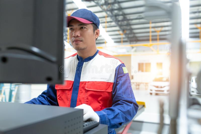 Fechado acima do mecânico asiático do homem no uniforme de uma auto roda: alinhamento de roda do computador M?quina de equil?brio imagem de stock