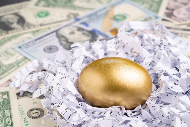 Fechado acima do ovo dourado no papel financeiro do fragmento do relatório com a pilha de cédulas dos dólares americanos usando-s fotografia de stock royalty free