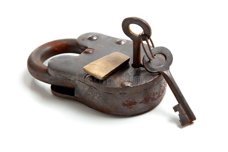 Fechamento antigo com chave de esqueleto no branco fotografia de stock royalty free