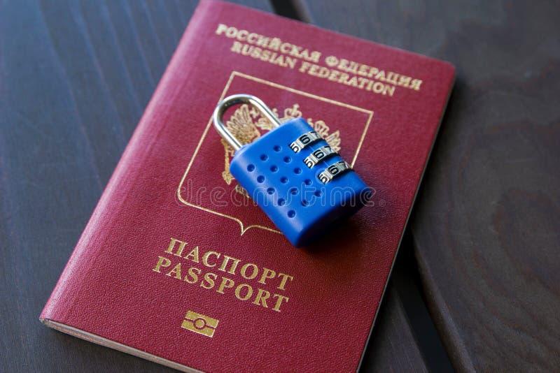 Fechamento azul que encontra-se no passaporte vermelho em um fundo de madeira, close-up foto de stock