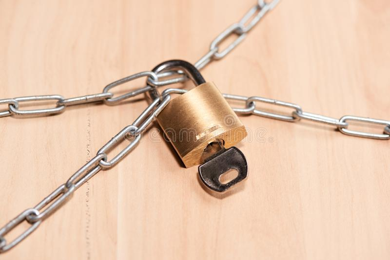 Fechamento chave travado com uma corrente na tabela fotografia de stock