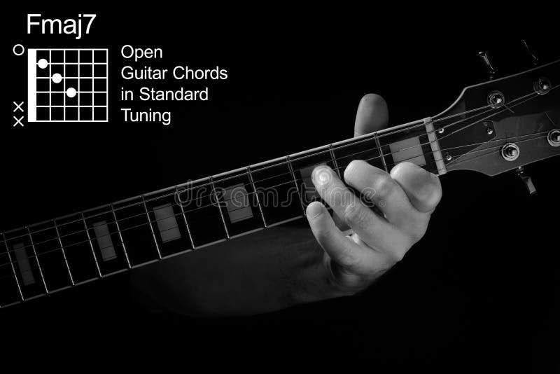 Fechamento da mão tocando o acorde FMaj7 no violão fotografia de stock