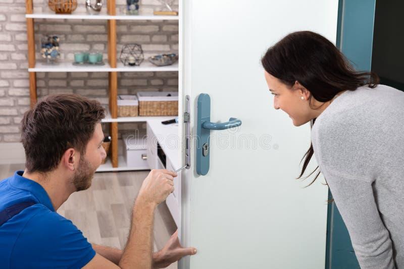 Fechamento de Fixing The Door do t?cnico com chave de fenda em casa fotos de stock royalty free
