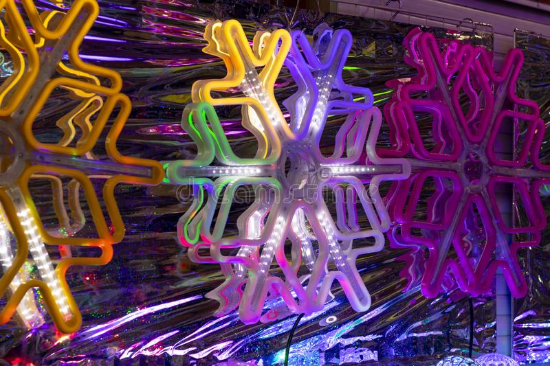 Fechamento néon snowflake sobre um fundo de folhas feito na escuridão total imagens de stock royalty free