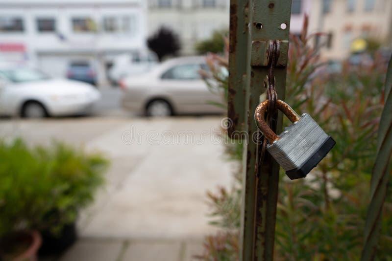 Fechamento oxidado na porta exterior que conduz ao passeio na área urbana imagens de stock