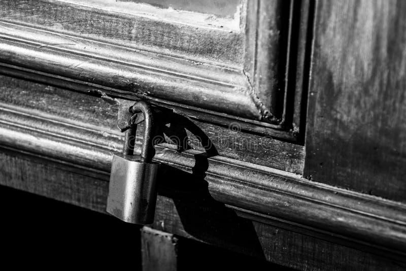 Fechamento velho em uma porta de madeira com o cadeado fechado oxidado, foto preto e branco do vintage imagens de stock