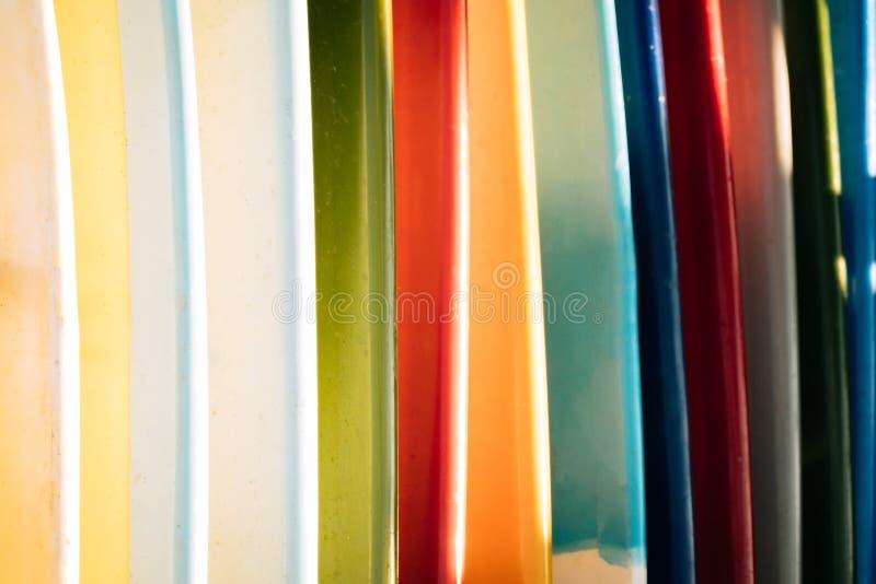 Fechar Conjunto de pranchas de surf de cores diferentes em uma pilha na praia arenosa para aluguel Placas de surfe multicoloridas foto de stock royalty free
