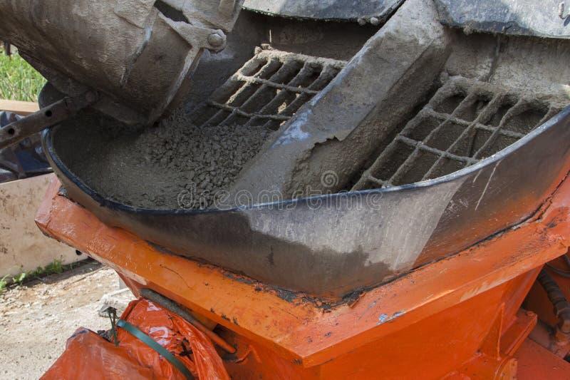 fechar a vista de passagem do betão da máquina de misturar betão para a bomba foto de stock