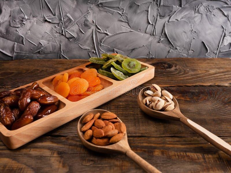 Fechas, albaricoques secados y kiwis en un plato de compartimiento y nueces en una cuchara de madera en una tabla de madera oscur fotos de archivo libres de regalías