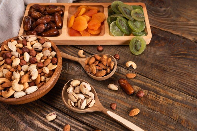 Fechas, albaricoques secados y kiwis en un plato y un surtido de compartimiento de nueces en cuenco de madera en una tabla de mad imágenes de archivo libres de regalías