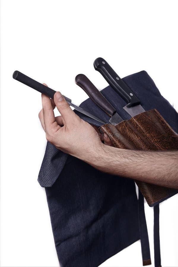 Feche acima, as mãos do homem que guardam o grupo de cozinhar facas fotos de stock royalty free