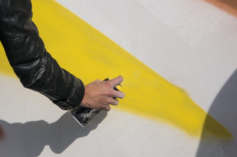 Feche acima com o menino novo que faz os grafittis, guardando o pulverizador foto de stock royalty free
