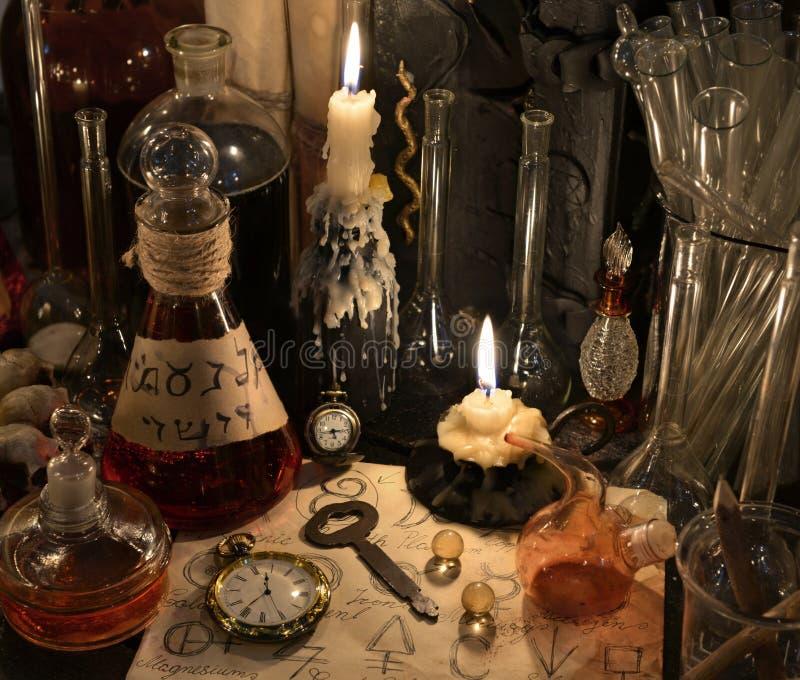 Feche acima com pulso de disparo, chave, vela, garrafas e objetos da mágica imagens de stock royalty free